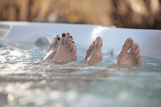 a-couples-toes-appear-out-of-the-water-in-a-close-up-image-2