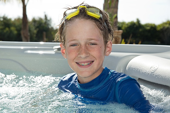 boy in a hot tub demonstrates best hot tub water care