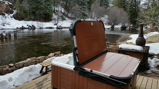 a customer image of a hot tub cover next to a beautiful river in the mountains