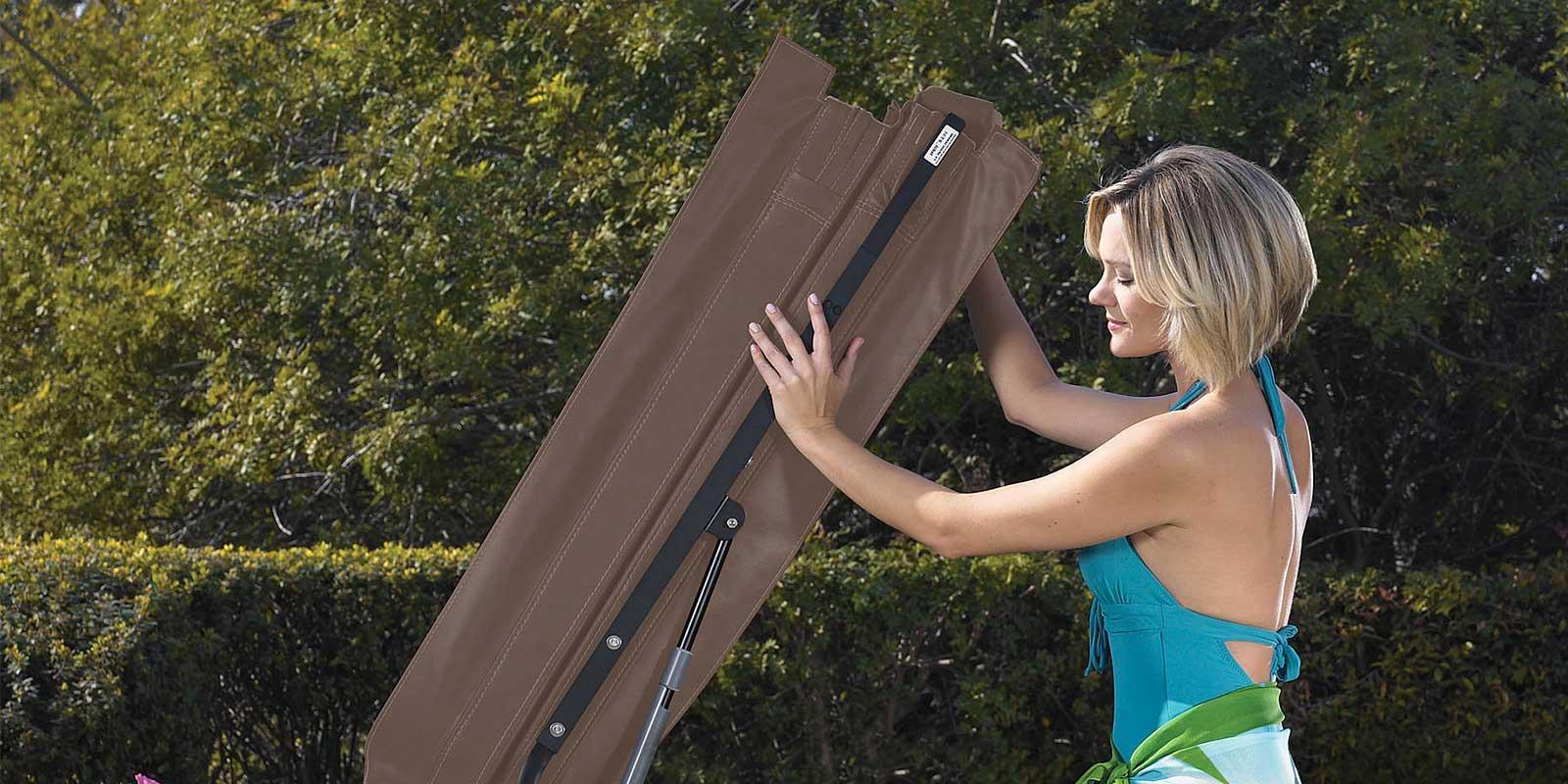 A woman is putting the cover on her Hot Spring Hot Tub